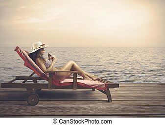 Woman relaxing on a beach during sunset