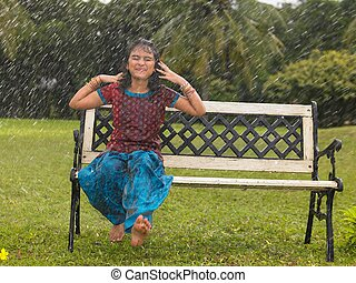 Asian kid playing in the rain