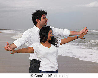 Asian couple standing by the beach