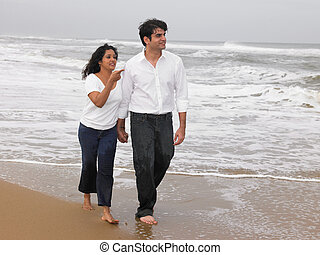 couple walking along the beach - Asian couple walking along...