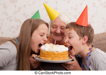 Senior woman and its grandsons with birthday cake