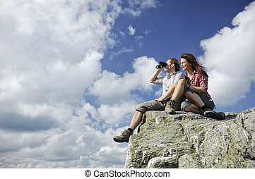 Two people sitting on top of a mountain, man looking with...