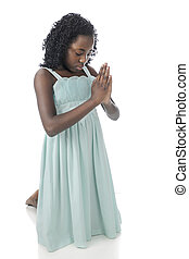 Kneeling in Prayer - A beautiful preteen kneeling in prayer,...