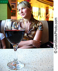 glass of red wine on the table and a girl