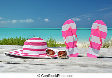 Hat, sunglasses and flip-flops against ocean Exuma, Bahamas
