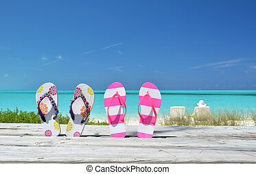Two pairs of flip-flops against ocean Exuma, Bahamas
