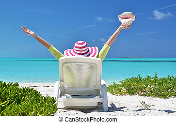 Girl with a shell on the sunbed looking to the ocean. Exuma,...