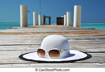 Hat and sunglasses on the wooden jetty Exuma, Bahamas