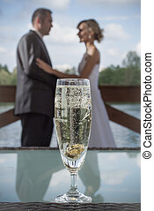 Closeup of wedding rings in a glass of champagne