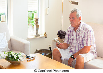 Senior man zapping remote control in modern bright living...