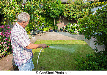Senior man watering his garden on a sunny day