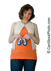 Pregnant adult woman playing with baby shoes