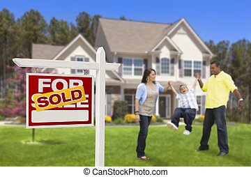 Hispanic Family in Front of Sold Real Estate Sign, House -...