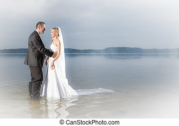 Happy young couple standing in a lake
