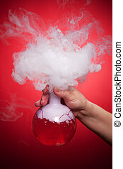 Steaming flask with red liquid in the hand on a red...