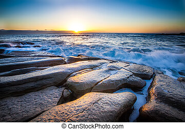 scenic sunrise - the breaking dawn over a rocky shore and...