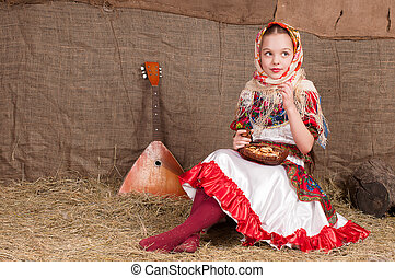 Russian girl in national dress, eating bagels and drinking...