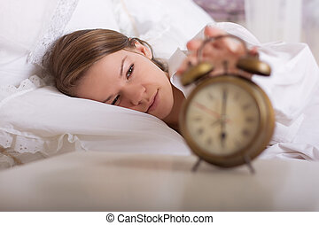 girl is sleeping and turns off the alarm at 6 am