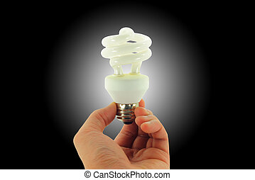 Light Bulb In Hand Isolated On Black With Spotlight