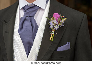 groom with purple flower buttonhole