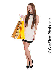 Happy Young Woman Holding Shopping Bags Over White...