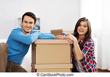 Portrait of young couple with moving boxes