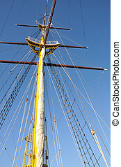 Mainmast of big sailboat with blue