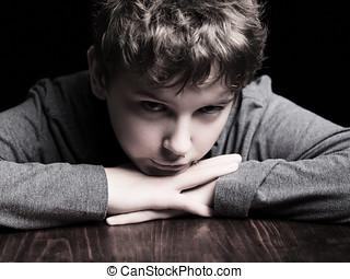 Sad teenage boy - Portrait sad teenage boy on a black...