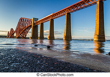 Train riding on the Forth Road Bridge at sunset