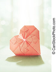 Stylized image of a paper origami heart with backlight and...