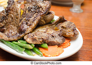 Lamb Chop with carrot slices on a white plate
