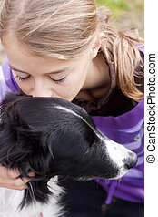 Child with dog - Close up of a pretty girl hugging a dog.