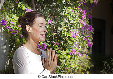 Mature woman doing yoga - Senior woman holding her hands...