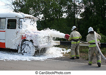 firefighters with foam extinguish a burning bus -...