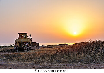 Bulldozer on the beach at sunset