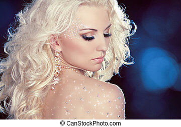 Glamour portrait of beautiful woman model with fashion makeup and romantic wavy hairstyle over night lights .