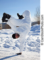 Soldier in white camouflage makes a break dance on the white...
