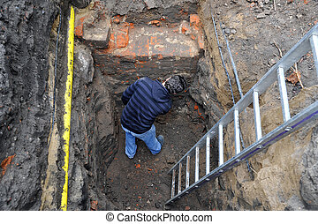 Archaeologist examines a medieval wall, part of a building,...
