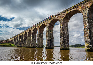 View of the train passing through the old stone bridge in...
