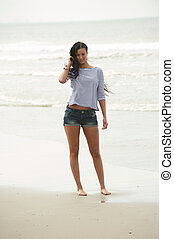 Portrait of a beautiful young woman standing barefoot on the beach