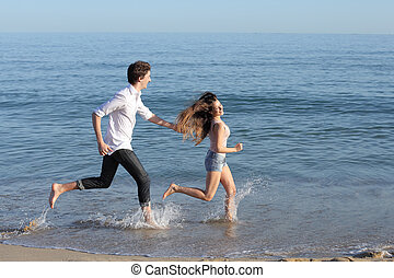 Couple chasing and running on the beach