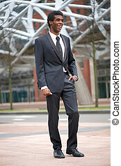 Portrait of a smiling african american businessman walking...