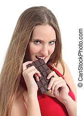 Portrait of a beautiful woman in red eating a chocolate bar...
