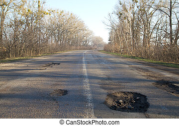 Bad road in holes after winter in Ukraine