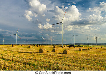 View of electric windmills in field