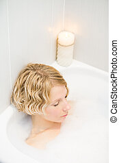 Young woman relaxing in the bath with candlelight