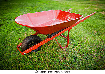 Red trolley on the lawn - Red wheelbarrow in the middle of...