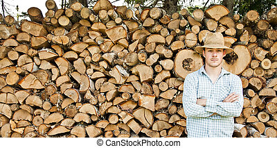 Woodcutter with straw hat on a background of wood