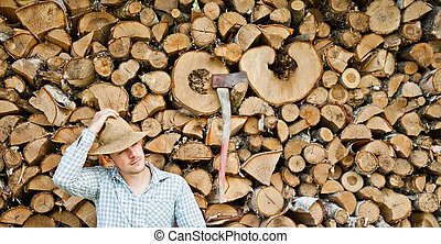 Woodcutter with straw hat on a background of wood taking a...