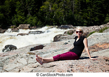 Young girl sitting on a rock and relaxing
